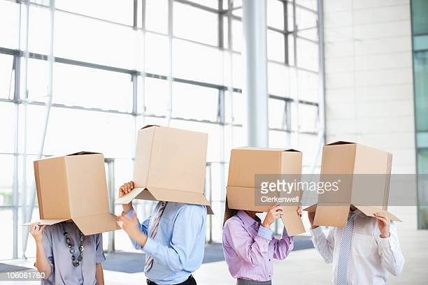 Business co-workers covering faces with cardboard boxes at new office