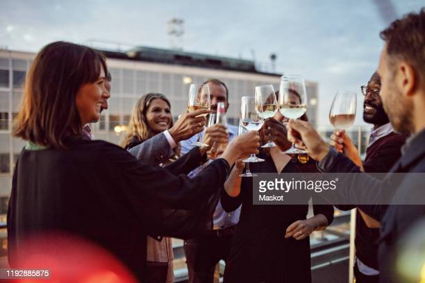 business coworkers toasting wineglasses while celebrating in office party on terrace - party social event stock pictures, royalty-free photos & images