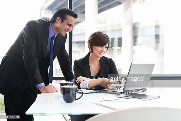 Business Coworkers Using Laptop During Meeting in Glass Office, Copyspace