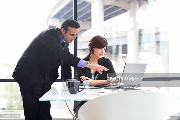 Business Coworkers Using Laptop During Meeting in Glass Office