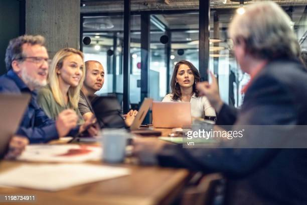 business discussions at a conference table - multi generation family stock pictures, royalty-free photos & images