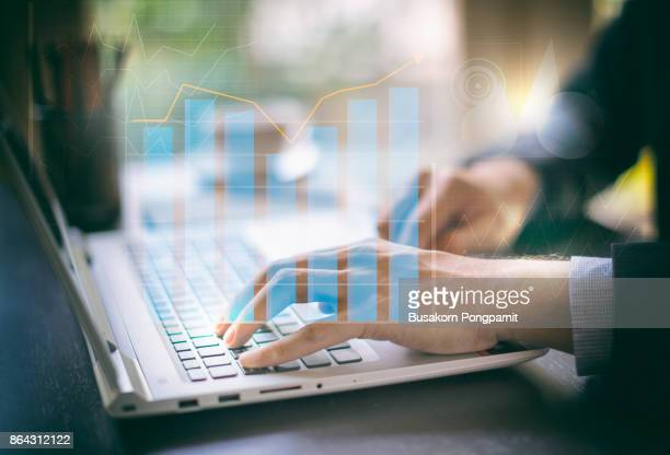 business documents on office digital computer laptop and graph financial with social network diagram and man working in the