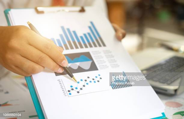 business documents on office table with smart phone and digital tablet and graph financial with social network diagram and man working in the background - information equipment stock pictures, royalty-free photos & images