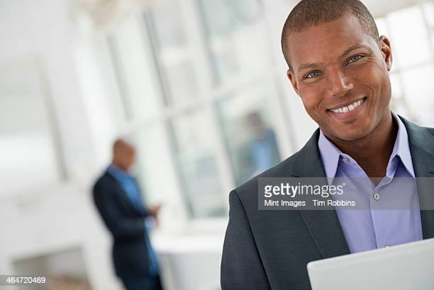 A business environment, a light airy city office. Business people. A young man in a suit using a digital tablet.