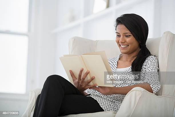 A business environment, a light and airy workplace in the city. A woman sitting on a sofa, using a digital tablet.