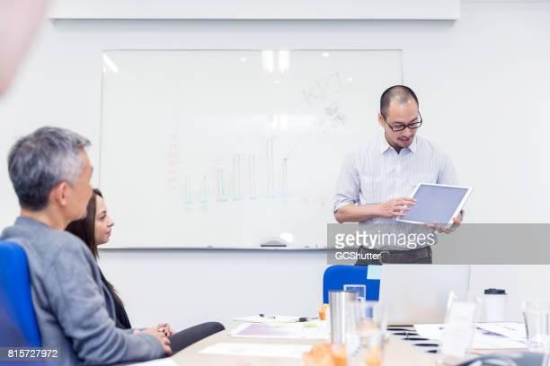彼のデジタル タブレットを使用してプレゼンテーションを行うビジネス エグゼクティブ - セールストーク ストックフォトと画像