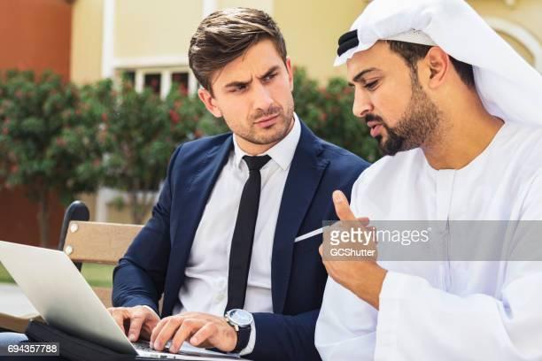 ejecutivo de negocios tener una conversación con un empresario árabe - cultura árabe fotografías e imágenes de stock