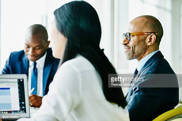 business executive listening during meeting - finance et économie photos et images de collection