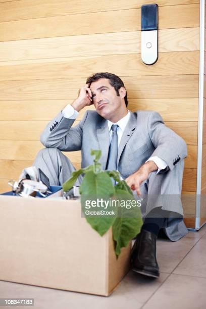 Executivo de negócios sentado em uma caixa de material de Escritório