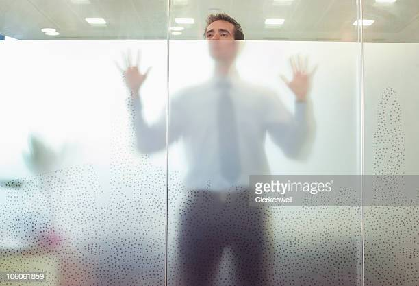 Business executive standing behind glass door