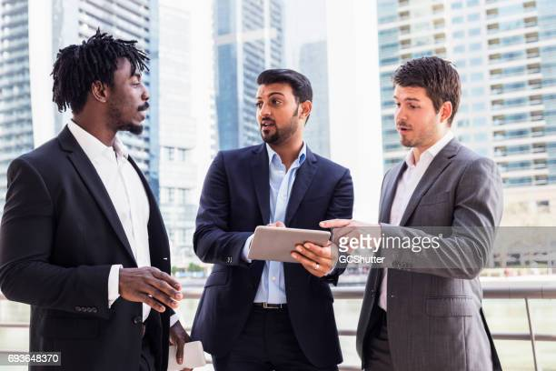 business executive using a digital tablet while discussing work with his colleagues - bahrain stock pictures, royalty-free photos & images