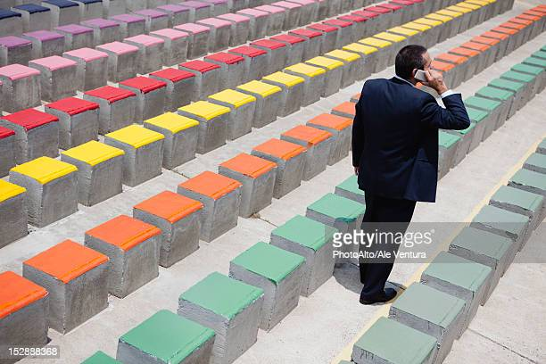 business executive using cell phone by rows of bleachers, rear view - multi colored suit stock photos and pictures