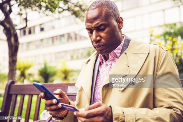 business executive using mobile phone and credit card for online reservation - credit score stock pictures, royalty-free photos & images