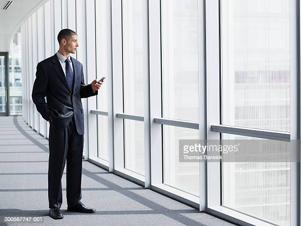 Business executive using PDA and looking out window