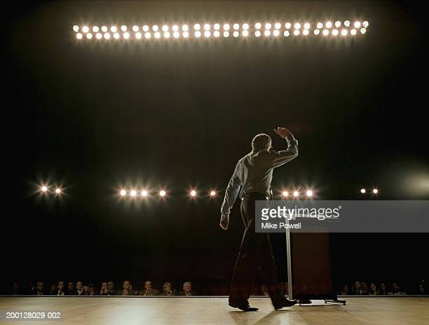 Business executive waving, walking towards podium on stage, rear view