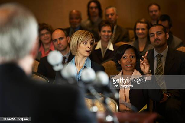 business executives at conference room, focus on woman with hand raised - press conference stock pictures, royalty-free photos & images