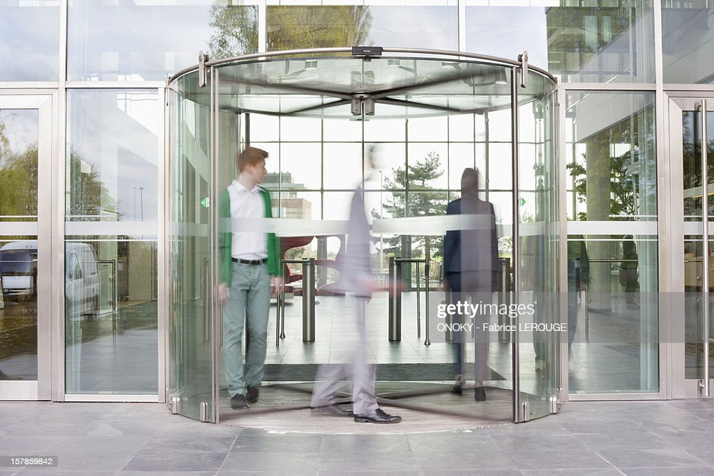 Business executives at entrance of an office building : Stock Photo