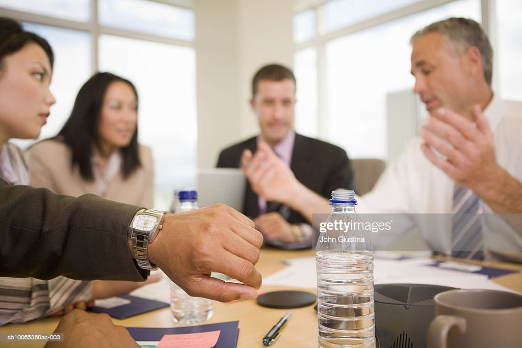 Business executives discussing at conference table, man looking at watch, (focus on foreground) : Foto stock