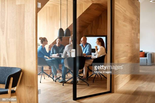 business executives discussing in office meeting - zakenbijeenkomst stockfoto's en -beelden