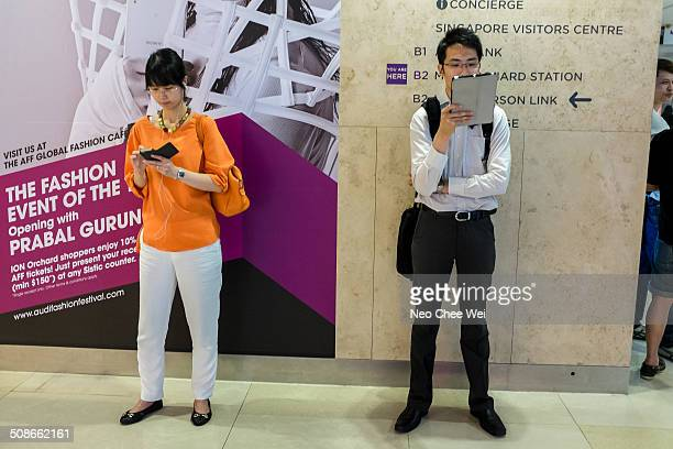Business executives engrossed in smart devices after work Man watching video clip while woman is text messaging Taken at Orchard MRT station Singapore
