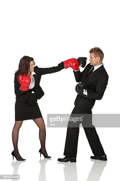 Business executives fighting in boxing gloves