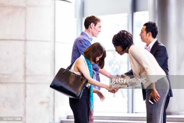 business executives greeting with respect - social grace stock pictures, royalty-free photos & images