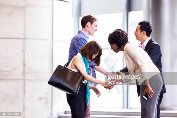 zakelijke managers groet met respect - social grace stockfoto's en -beelden