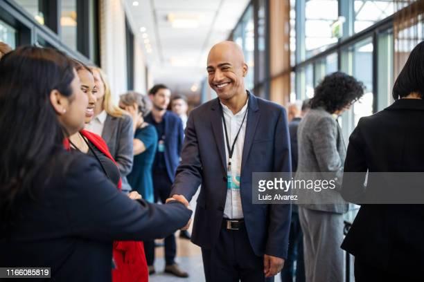 business executives handshaking at convention center - centro congressi foto e immagini stock