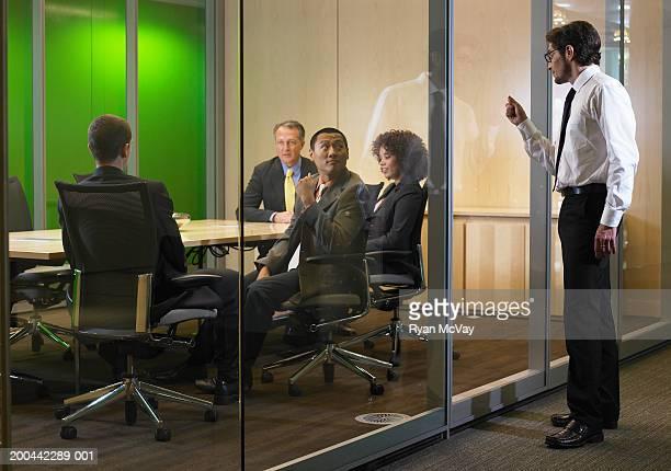 business executives in meeting, man interrupting  with knock on glass - exclusión fotografías e imágenes de stock