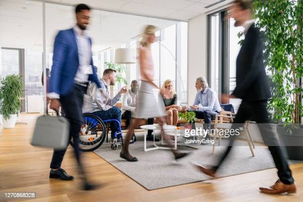 business executives on the move through modern office - focus on background stock pictures, royalty-free photos & images