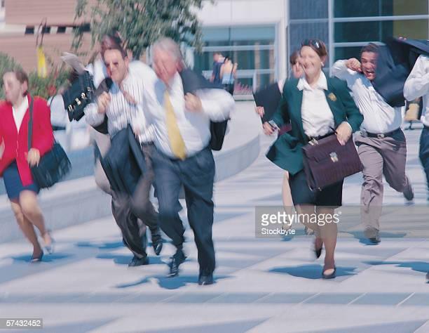 business executives running on a city sidewalk
