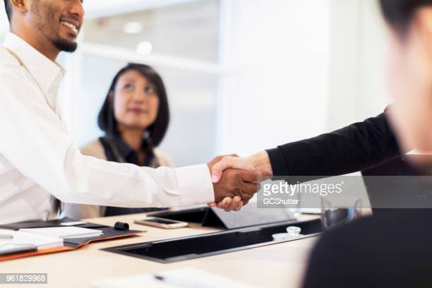business executives shaking hand on a new business agreement - executive director stock pictures, royalty-free photos & images
