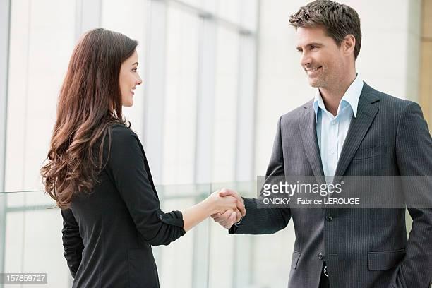 business executives shaking hands in an office - schütteln stock-fotos und bilder