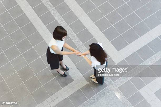 Business executives shaking hands, overhead view