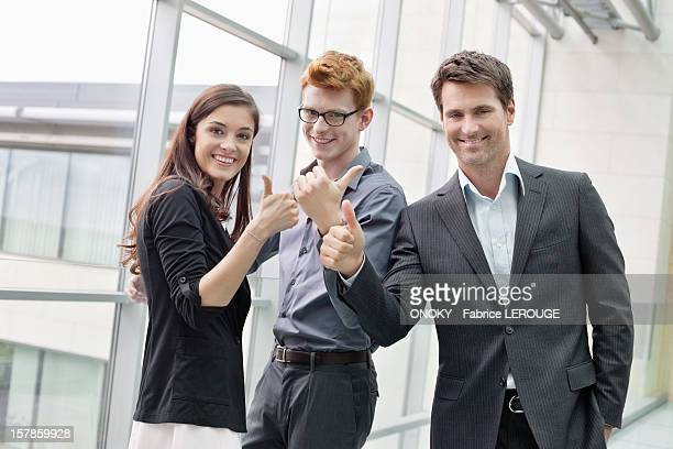 Business executives showing thumbs up and smiling in an office