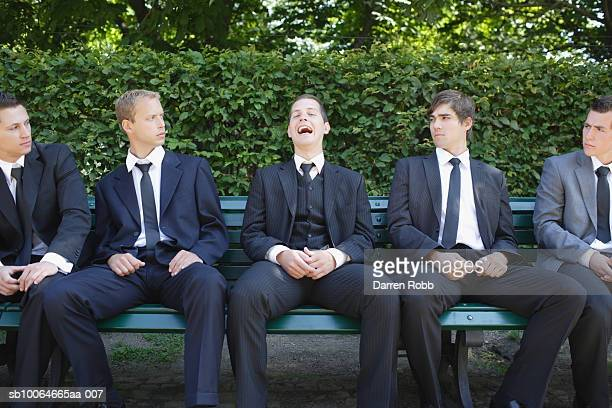 Business executives sitting on bench in park, one laughing