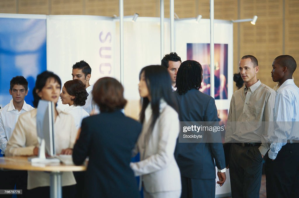 Business executives standing in exhibition hall : Stock Photo