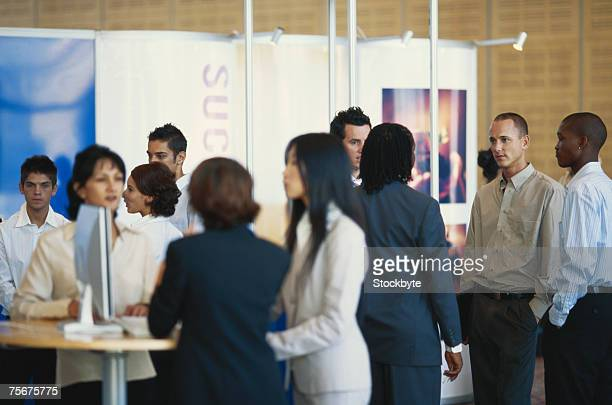 business executives standing in exhibition hall - messen stock-fotos und bilder