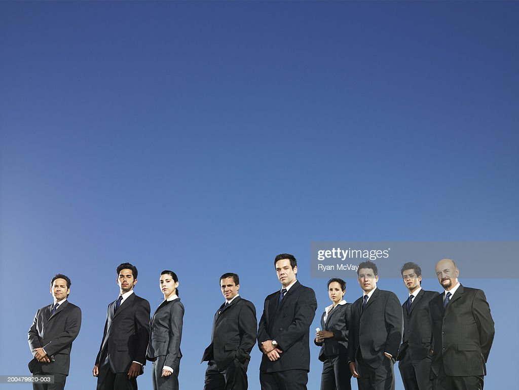 Business executives standing in field, blue sky background : Foto de stock