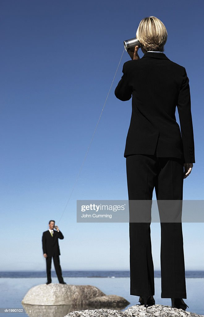 Business Executives Standing on Rocks in the Sea, Communicating Through Two Tin Cans Connected by String : Stock Photo