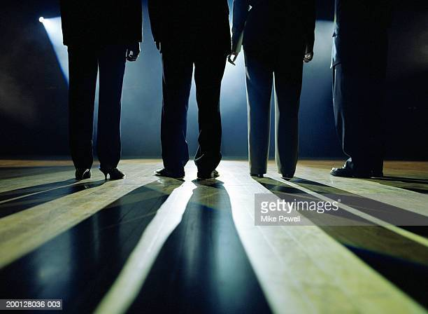 Business executives standing on stage facing spotlight, rear view
