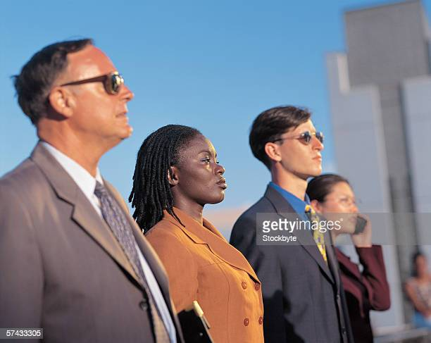 business executives standing outdoors in a row