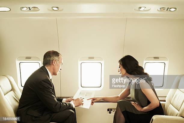 Business executives talking aboard private jet