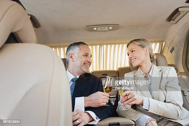Business executives toasting in limousine