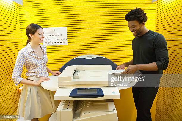 Business executives using photocopy machine in an office