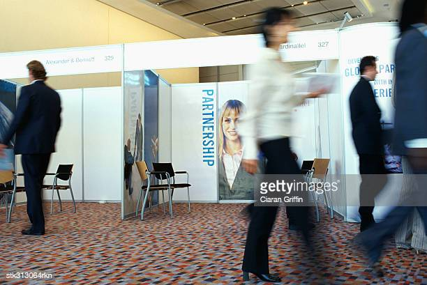 business executives walking at an exhibition - tradeshow stock pictures, royalty-free photos & images