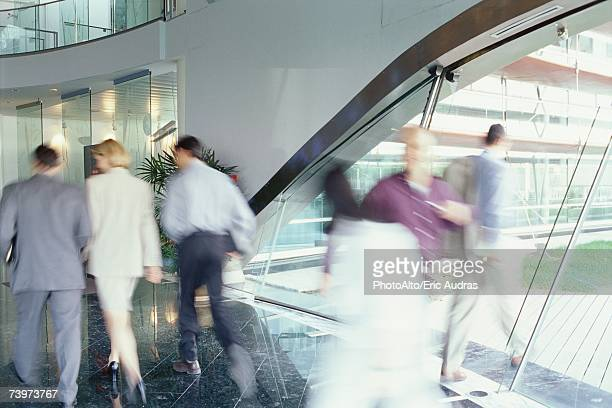 Business executives walking in lobby, blurred motion