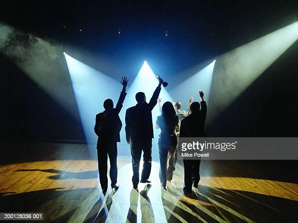 Business executives walking on stage towards spotlight, holding award