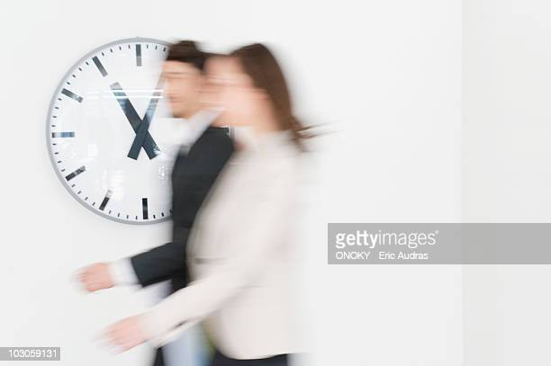 Business executives walking together in front of a wall clock