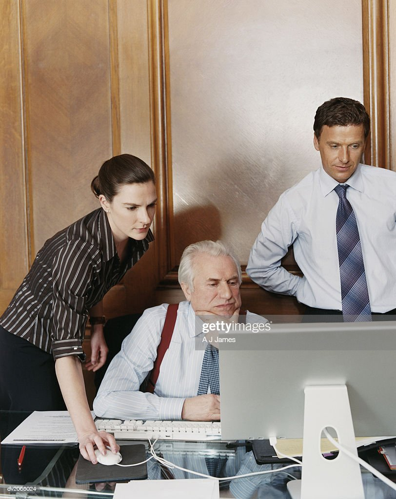 Business Executives Working Around a CEO's Desk : Stock Photo